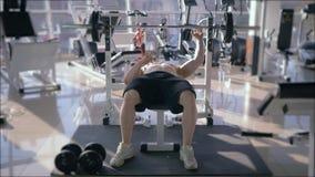 Treinamento do halterofilista, imprensa de banco fazendo desencapado-chested do homem muscular forte com o poder do quando do bar video estoque