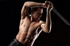 Treinamento do homem forte com a espada antiga no preto imagem de stock