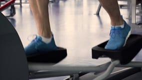 Treinamento do homem novo na máquina elíptica no Gym vídeos de arquivo