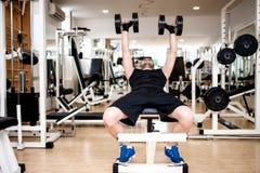 Treinamento do homem novo no gym com dumbbel imagem de stock