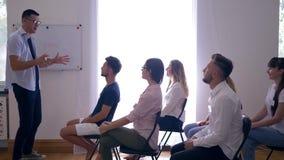 Treinamento do negócio, treinador que explica o desenvolvimento de ideias do negócio para colegas na aprendizagem ativa no seminá video estoque
