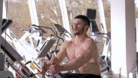 Treinamento do poder, homem do halterofilista com exercício fazendo desencapado-chested da construção do músculo no simulador da  filme