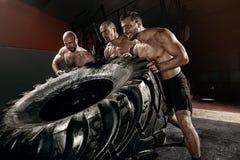 Treinamento do trongman de Crosss - três homens que lançam o pneu Imagem de Stock Royalty Free