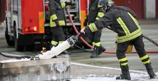 Treinamento e fogo do sapador-bombeiro - extinguindo com espuma e caminhão fotografia de stock