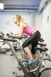 Treinamento escandinavo louro caucasiano da menina da aptidão na bicicleta no gym imagens de stock