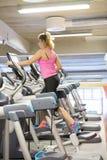 Treinamento escandinavo louro caucasiano da menina da aptidão no crosstrainer no gym imagem de stock