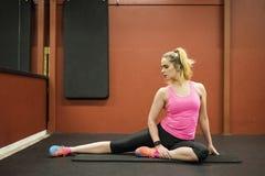 Treinamento escandinavo louro caucasiano da menina da aptidão no gym que faz a ioga imagens de stock