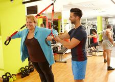 Treinamento excesso de peso da mulher com instrutor pessoal fotos de stock