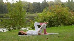 Treinamento exterior da aptidão da mulher bonita nova do ajuste que faz o exercício para os pés vídeos de arquivo