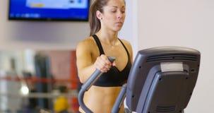 Treinamento focalizado da mulher na máquina do exercício da elipse no gym da aptidão filme