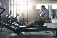 Treinamento funcional Homem que faz o exercício na máquina de enfileiramento no Gym fotografia de stock