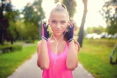 Treinamento louro de sorriso da menina no crepúsculo no parque urbano e na escuta Imagens de Stock