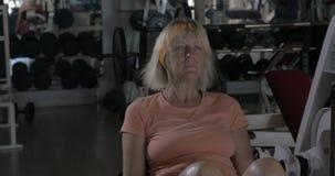 Treinamento maduro da mulher na máquina traseira da extensão vídeos de arquivo