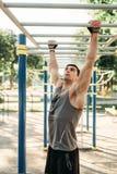 Treinamento masculino do atleta nas barras horizontais exteriores foto de stock royalty free