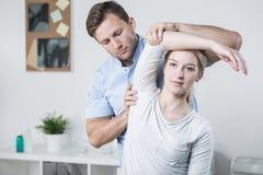 Treinamento masculino do fisioterapeuta com paciente imagem de stock