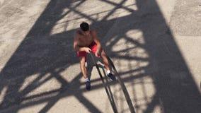 Treinamento muscular descamisado do homem com as cordas da batalha internas contra o céu azul video estoque