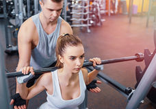 Treinamento novo, bonito da menina com o treinador no gym fotos de stock