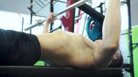 Treinamento profissional forte do halterofilista do homem novo com a imprensa de banco do Barbell video estoque