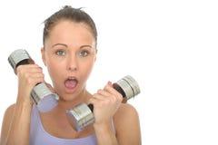Treinamento saudável da jovem mulher com os pesos que olham chocados Fotografia de Stock