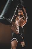Treinamento tailandês muay concentrado do lutador com saco de perfuração Foto de Stock Royalty Free