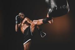 Treinamento tailandês muay focalizado do lutador com saco de perfuração Imagem de Stock