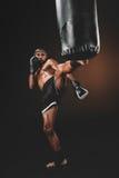 Treinamento tailandês muay irritado do lutador com saco de perfuração Imagem de Stock