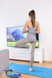 Treinamento video da mulher da ioga na sala de visitas home fotografia de stock