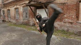 Treinamento violento do bandido com o bastão de beisebol que faz o pontapé à câmera filme