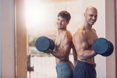 Treinando dois homens com pesos os músculos do braço fotos de stock