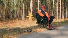 Treinando um atleta nos skateres do rolo Passeio do Biathlon nos esquis do rolo com polos de esqui, no capacete outono imagem de stock royalty free