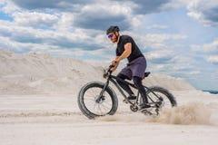 Treinando um ciclista em uma pedreira gredosa Um homem brutal em uma bicicleta gorda imagem de stock royalty free