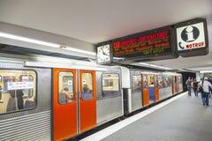 Treine com os passageiros que esperam em uma plataforma da estação Fotografia de Stock Royalty Free