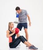 Treine a gritaria através do altifalante em uma mulher a fazer exercícios Fotos de Stock Royalty Free