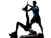 Treine a mulher do homem que exercita abdominals com silhueta do bosu Fotografia de Stock
