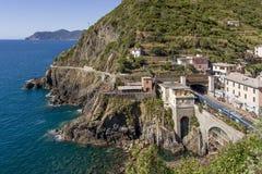 Treine no estação de caminhos-de-ferro de Riomaggiore com La do ` através do ` no fundo, Cinque Terre do amore do ` do dell, Ligu fotografia de stock royalty free