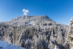 Treine o viaduto Langwies em Suíça na luz do sol, inverno, neve, Fotografia de Stock