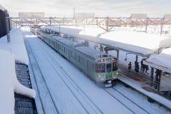 Treine a parada na estação de trem com neve do inverno em Japão Fotografia de Stock