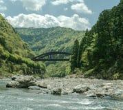 Treine a ponte entre os montes ao longo do rio de Hozugawa fotografia de stock royalty free