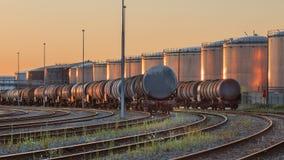Treinen met silo's van een petrochemische die installatie op de achtergrond door warm licht, Haven wordt aangestoken van Antwerpe royalty-vrije stock foto's