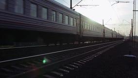 Treinpassen door Spoorweg bij Zonsondergang stock footage