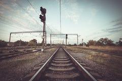 Treinplatform en verkeerslicht bij zonsondergang Spoorweg Spoorweg st Stock Fotografie