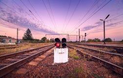 Treinplatform en verkeerslicht bij zonsondergang Spoorweg Spoorweg st Stock Afbeeldingen