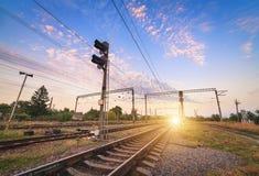 Treinplatform en verkeerslicht bij zonsondergang Spoorweg Spoorweg st Stock Foto