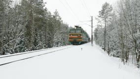 Treinritten per spoor in de winterbos tijdens de sneeuwstorm stock videobeelden