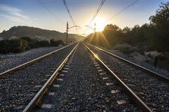 Treinsporen bij zonsondergang met heldere zon en metaalbezinningen stock afbeelding