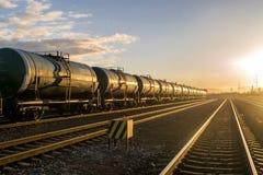Treinsporen en treinwagens bij een zonsondergang stock afbeeldingen