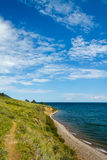 Trek on the coastline of Baikal lake. Small trekking path at Baikal lake with blue skies Royalty Free Stock Image