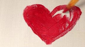 Trek een hart met een borstel op het canvas stock footage