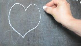 Trek op het bord met krijt Wij trekken een hart stock footage