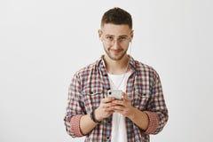 Trek ` t u aan ziet ik in oortelefoons ben Gehinderd knap jong mannetje die met baard van onder voorhoofd camera bekijken terwijl royalty-vrije stock fotografie